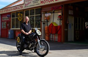 Colin Melhuish enjoys any excuse to ride the AJS here outside a very 'in-period' garage display at Amberley Museum